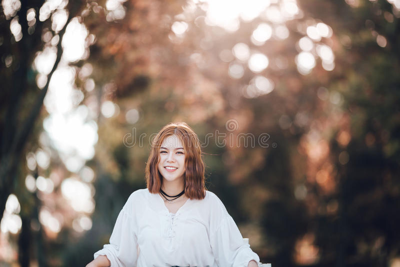 Portrait of young hipster Asian girl Laugh and smiling posing in the autume park forest background royalty free stock photos