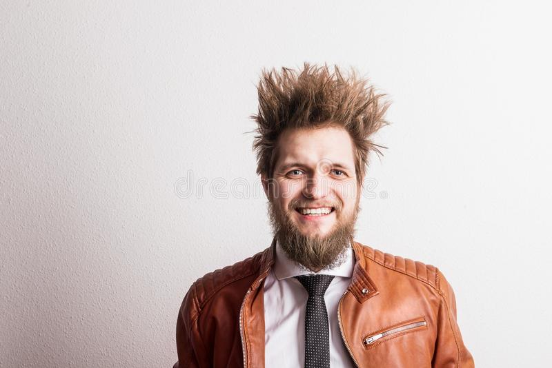 Portrait of a young hipster man with messy hairstyle in a studio. Copy space. royalty free stock image
