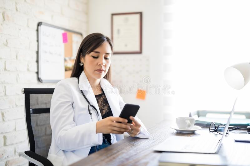 Doctor texting on phone royalty free stock photography