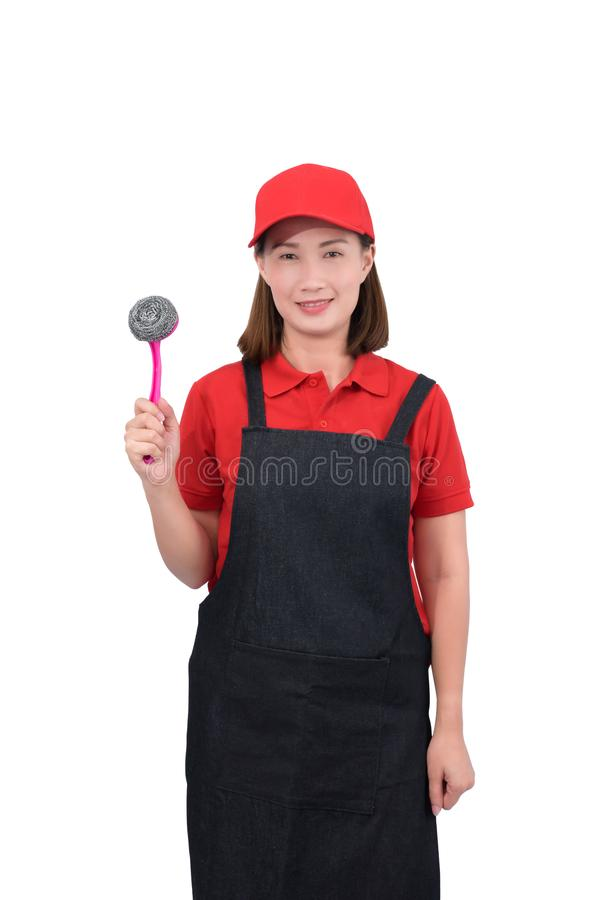 Portrait of young housekeeper smiling in red uniform with apron hand holding Scrub brush isolated on white backround royalty free stock photography