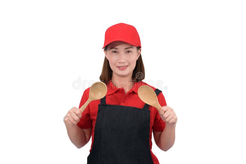 Portrait of young housekeeper smiling in red uniform with apron hand holding Wooden ladle isolated on white backround royalty free stock photos