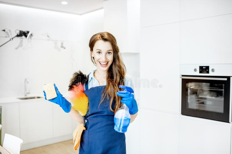 Portrait of a young housemaid with cleaning tools at home royalty free stock image