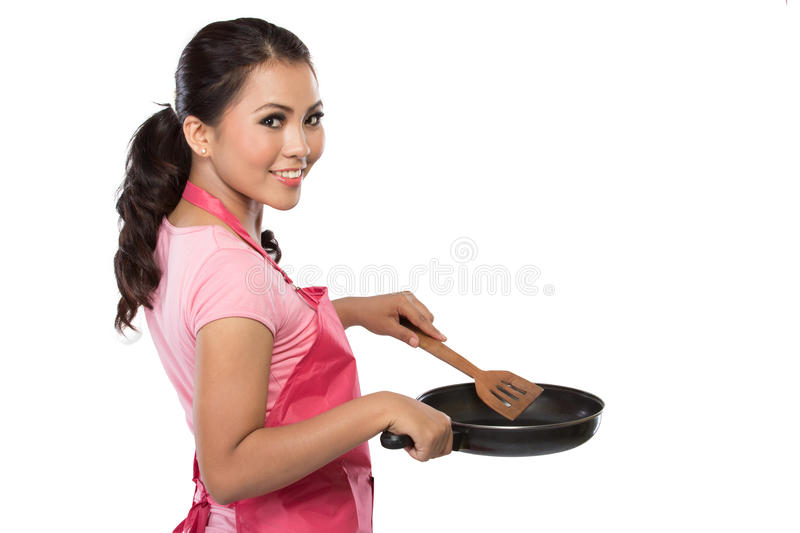Portrait of a young housewife ready to cook. Isolated over white background stock photography