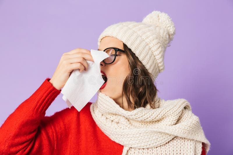 Young ill woman wearing winter hat isolated over purple background holding napkin. Portrait of a young ill woman wearing winter hat isolated over purple stock photo