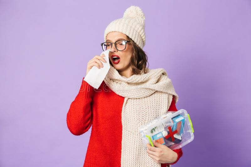 Young ill woman wearing winter hat isolated over purple background holding napkin. Portrait of a young ill woman wearing winter hat isolated over purple stock photography
