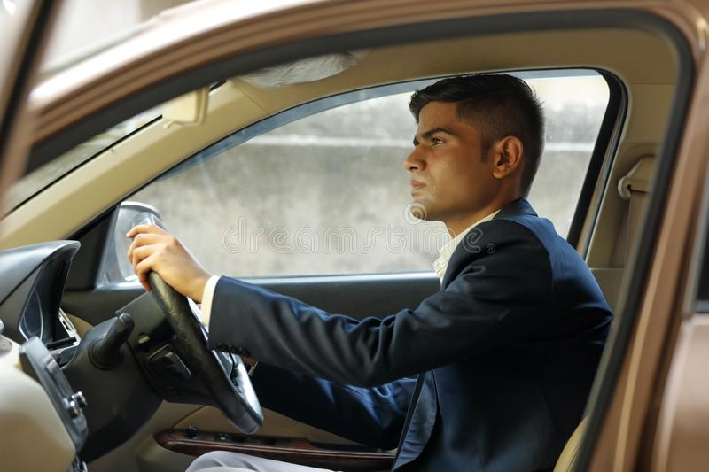 Portrait of young Indian business man, driving a car royalty free stock image