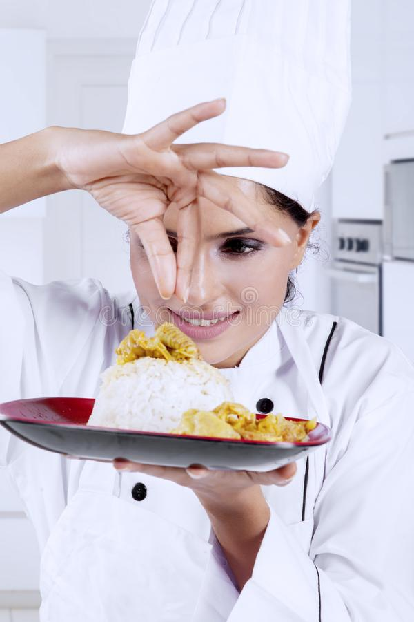 Indian chef sprinkling spices on a dish. Portrait of young Indian chef sprinkling spices on a dish while standing in the studio stock photos