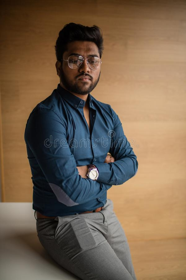 Portrait of a young Indian mam in spectacles posing agaist window stock photo