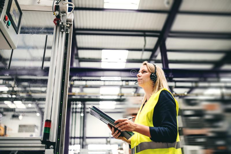 An industrial woman engineer with headset and clipboard in a factory, working. A portrait of a young industrial woman engineer with headset and clipboard in a royalty free stock photos