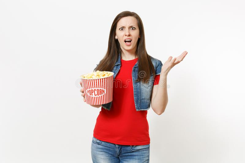 Portrait of young irritated dissatisfied brunette woman in casual clothes watching movie film, holding bucket of popcorn royalty free stock photography