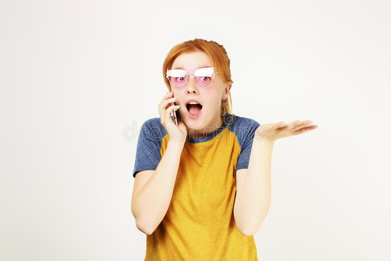 Beautiful red headed young woman posing, showing emotional facial expressions and making funny faces with mobile phone royalty free stock photo