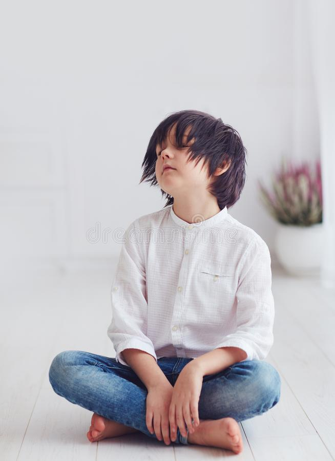 Portrait of young boy, anime character, sitting barefoot on the floor. Portrait of young kid, boy, anime character, sitting barefoot on the floor royalty free stock images