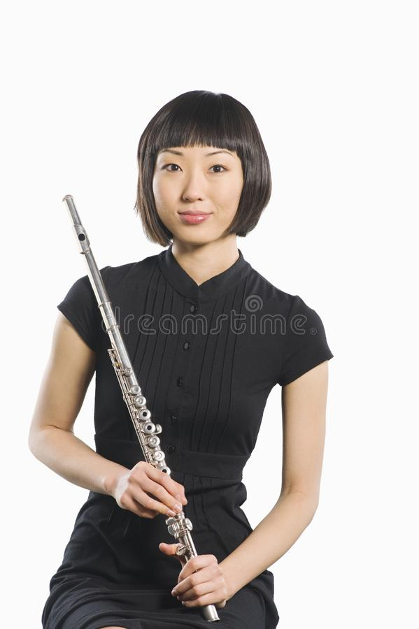 Portrait Of Young Korean Woman Holding Flute. Portrait of a beautiful Korean woman sitting with flute isolated over white background stock image