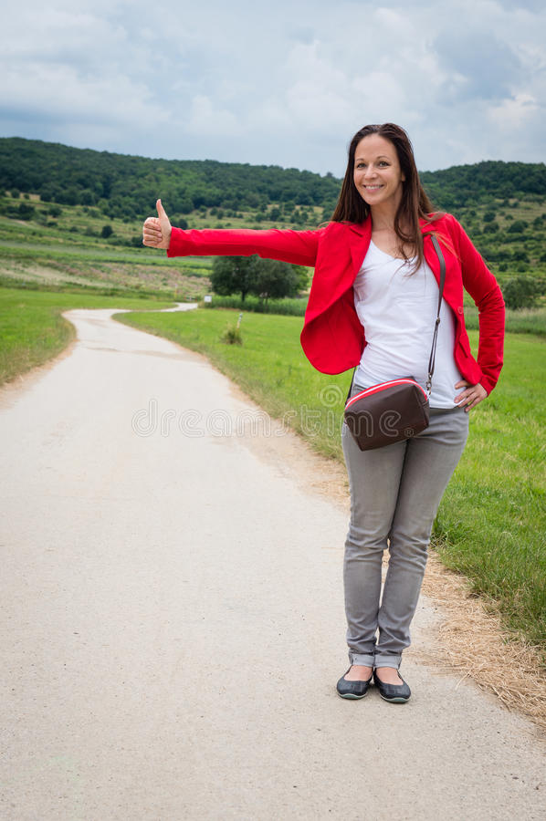 Portrait of young lady hitchhiking by the road. Portrait of young lady in red jacket hitchhiking by the road royalty free stock image