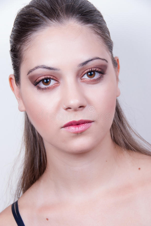 Portrait of young lady with nice skin and make up. Portrait of young lady with nice smooth clean skin with a make up, looking at the camera, hair gathered back stock photography