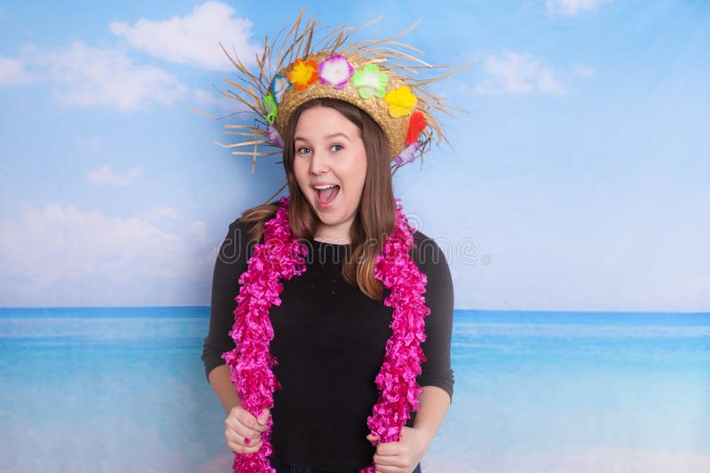 Portrait of young lady photo booth props beach ocean theme. Portrait of young lady wearing a straw hat and pink boa photo booth props beach ocean theme stock photography