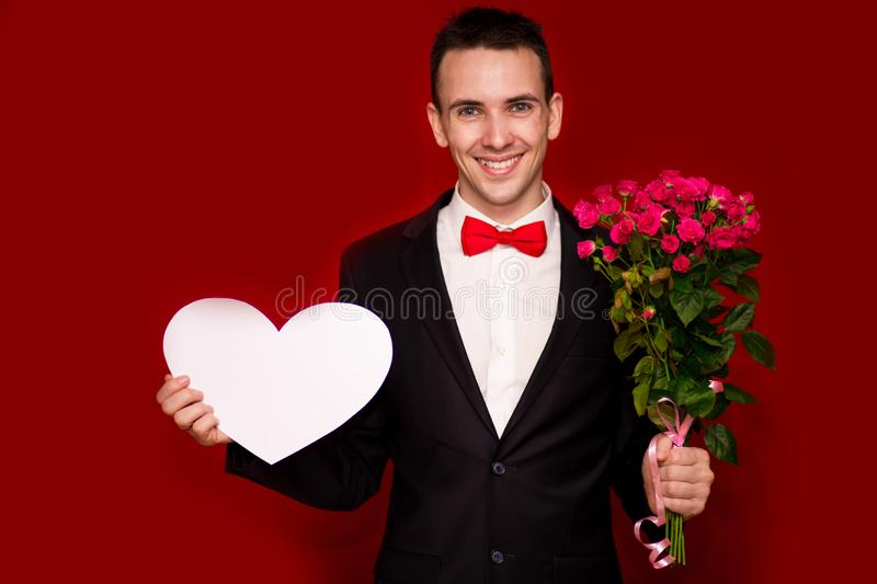 Portrait of young laughing businessman with flowers and big paper heart isolated on red. Background royalty free stock image