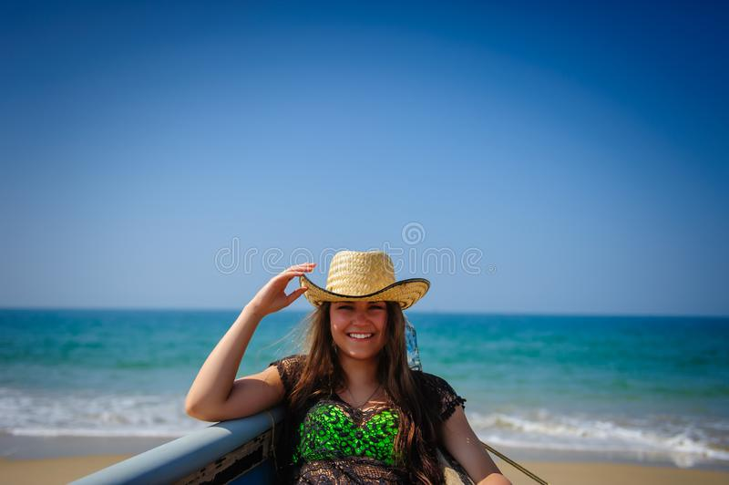 Portrait of young laughing girl with beautiful white teeth on a background of sandy beach, turquoise sea and bright blue sky royalty free stock images