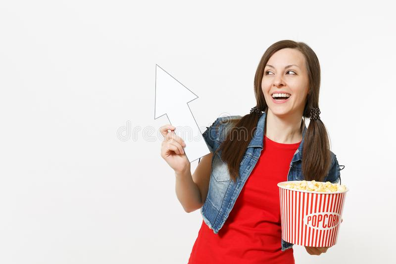 Portrait of young laughing woman in casual clothes watching movie film, holding bucket of popcorn, pointing white arrow. Up on copyspace isolated on white royalty free stock photos