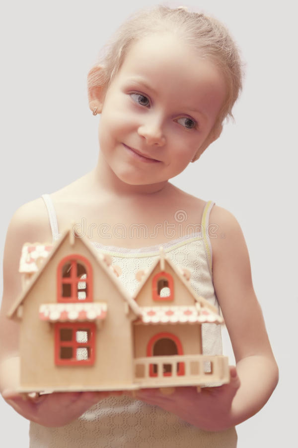 Portrait of young little girl holding scale house model. Showing dreaming facial expression. isolated stock image