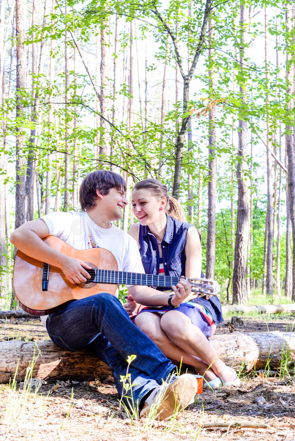 Portrait of young loving happy couple with guitar in forest. royalty free stock photography