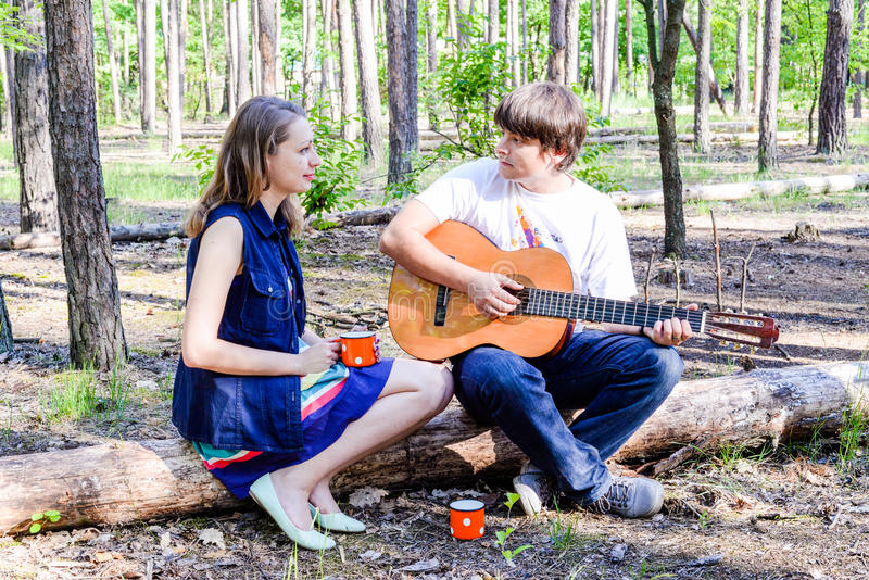 Portrait of young loving happy couple with guitar in forest. royalty free stock image