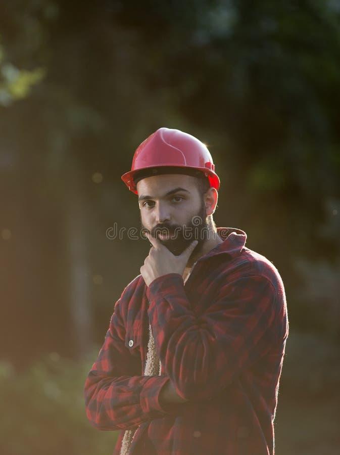 Lumberjack with beard and helmet. Portrait of young lumberjack with beard and helmet stock photo