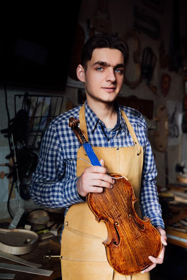 Portrait of a young luthier with a handcrafted violin in his workshop with the tools. Portrait of a young luthier with a handcrafted violin in his workshop with stock photos