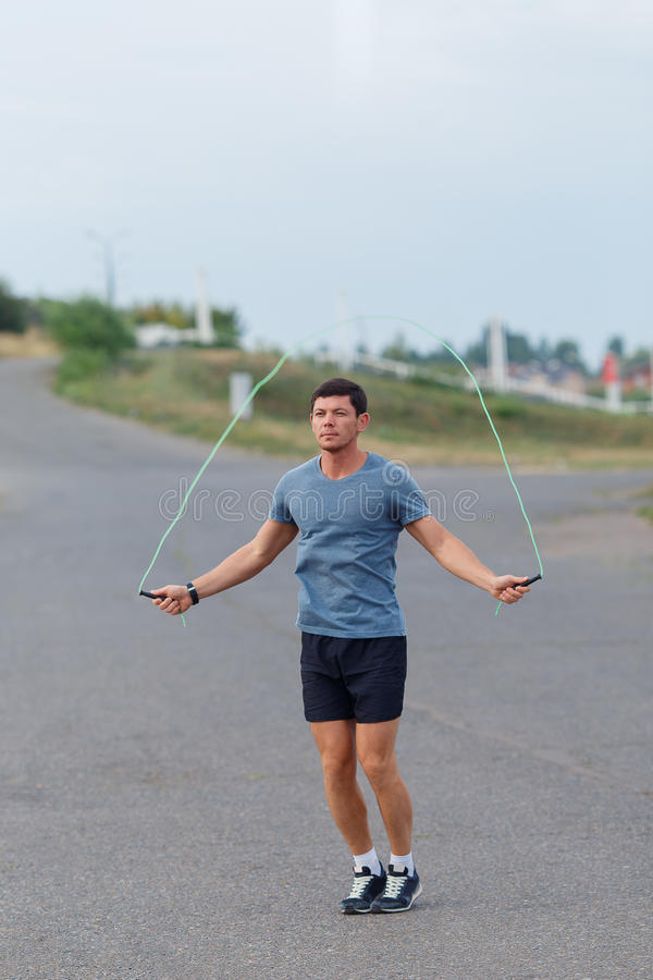 Portrait of young male athlete skipping rope outdoors. Portrait of young male athlete skipping rope outdoors royalty free stock photos