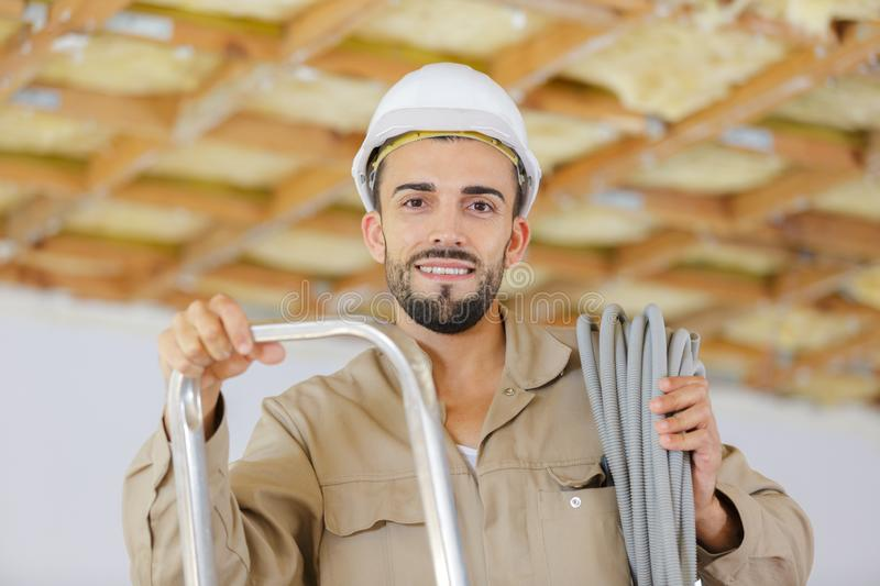 Portrait young male builder on stepladder stock photo
