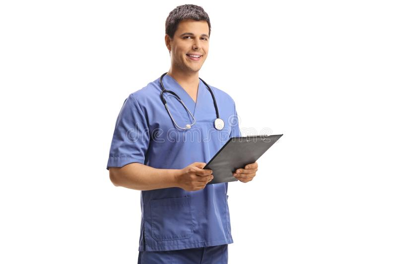 Portrait of a young male doctor in a blue uniform holding a clipboard and looking at the camera royalty free stock image