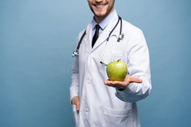 Portrait Of Young Male Doctor Holding Green Apple. Isolated On Light Blue. stock image
