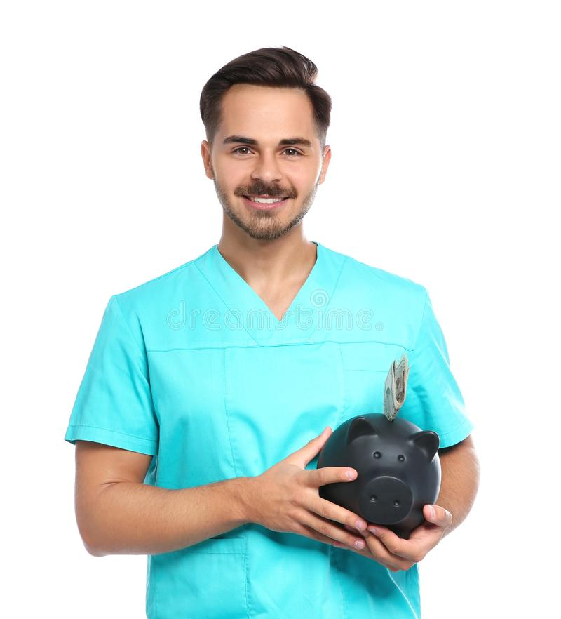 Portrait of young male doctor holding piggy royalty free stock image