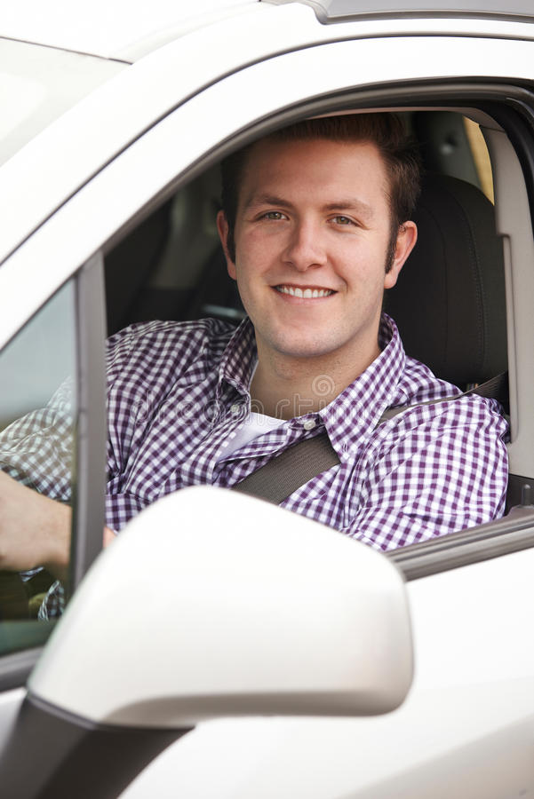 Portrait Of Young Male Driver Looking Out Of Car Window. Portrait Of Male Driver Looking Out Of Car Window royalty free stock photography