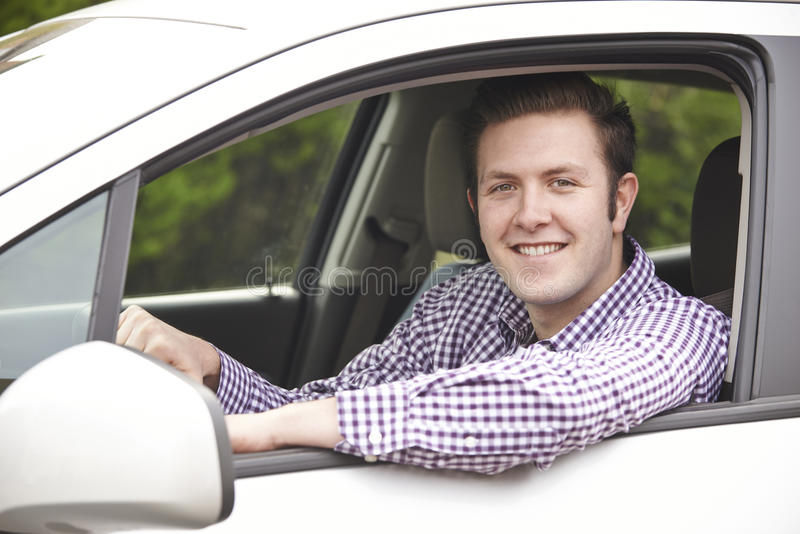 Portrait Of Young Male Driver Looking Out Of Car Window. Portrait Of Smiling Young Male Driver Looking Out Of Car Window royalty free stock images