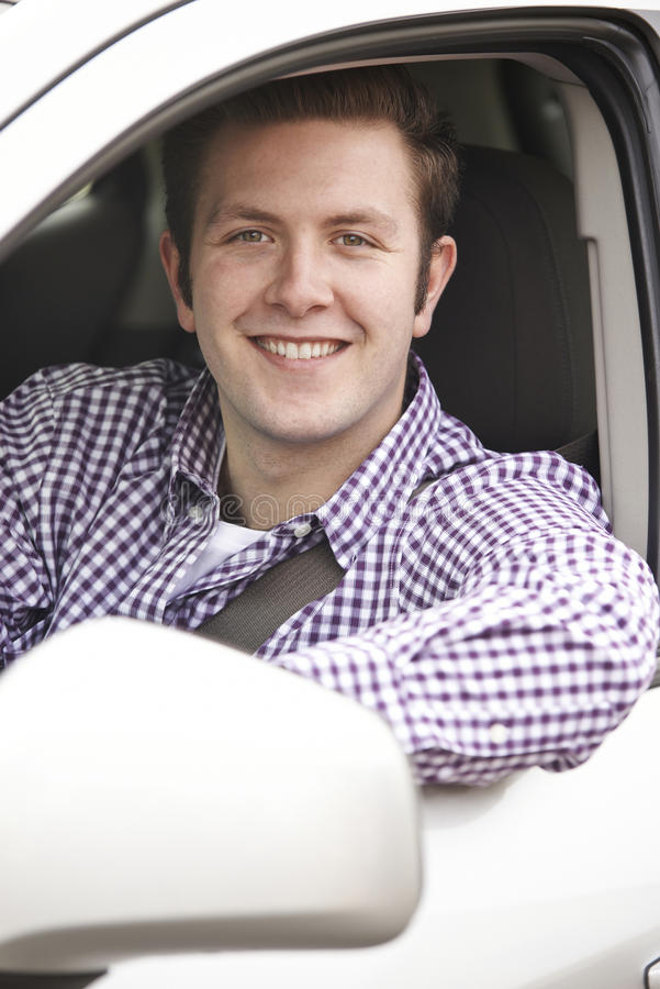 Portrait Of Young Male Driver Looking Out Of Car Window. Portrait Of Smiling Young Male Driver Looking Out Of Car Window stock photography