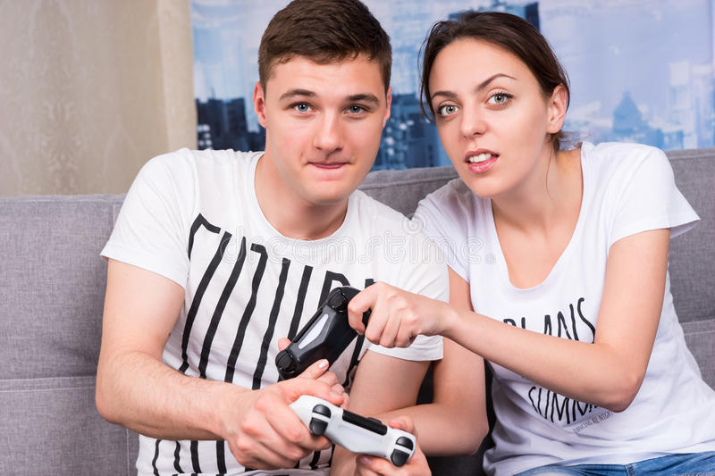 Portrait of young male and female gamers playing video game. Sitting on a couch together at home in a relaxed atmosphere stock images