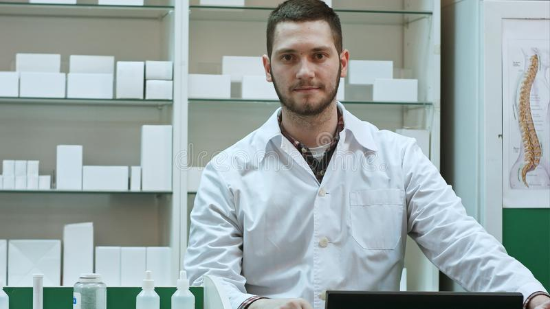 Portrait of young male pharmacist looking at camera and smiling stock images