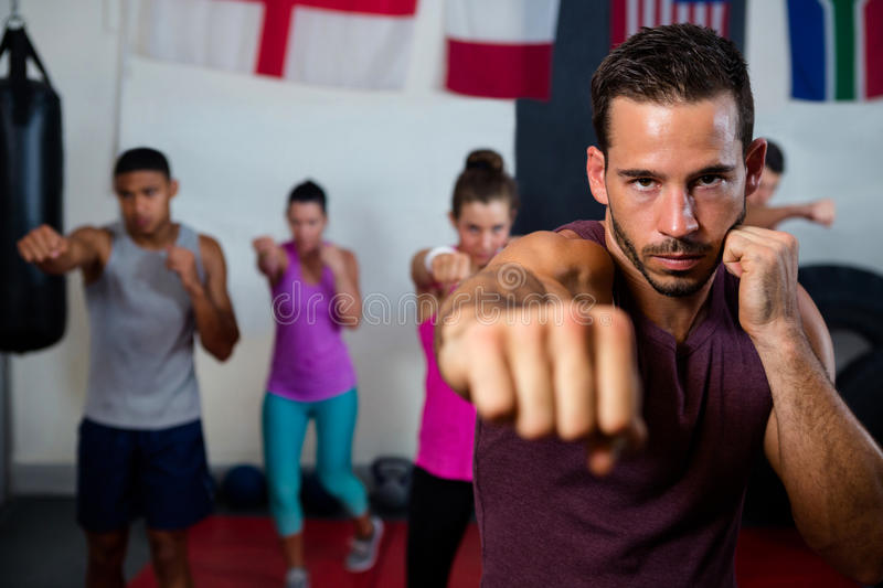 Portrait of young male practicing boxing against flags royalty free stock photos