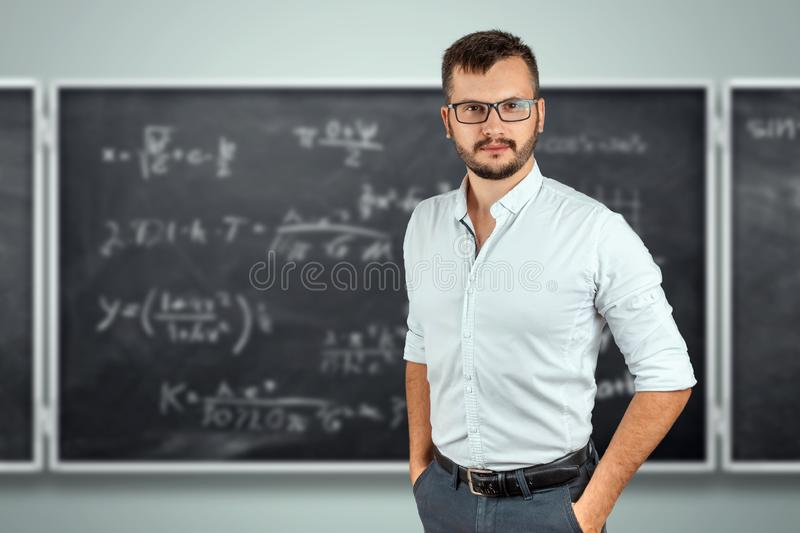 Portrait of a young male teacher on the background of the school blackboard. Teacher`s Day Knowledge Day back to school study royalty free stock image