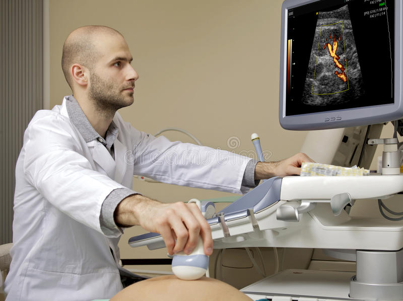 Portrait of young male technician operating ultrasound machine. In white dress royalty free stock images