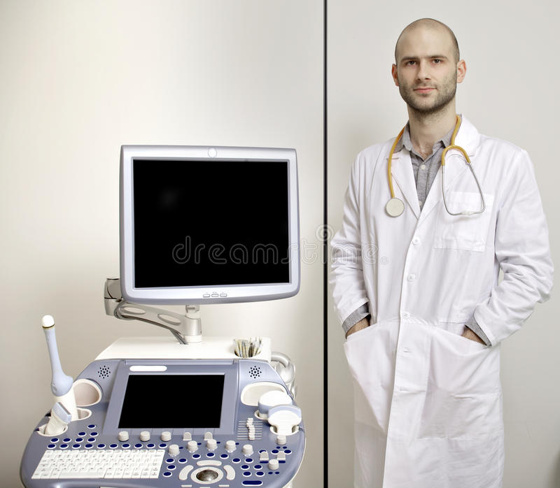Portrait of young male technician operating ultrasound machine. In white dress stock photos