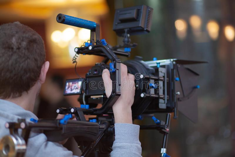 Young male video cameraman, photographer, shoots video or takes a photo on the camera stock image