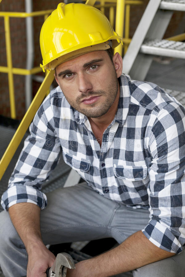 Portrait of young male worker in hard hat sitting on steps at industry royalty free stock photo