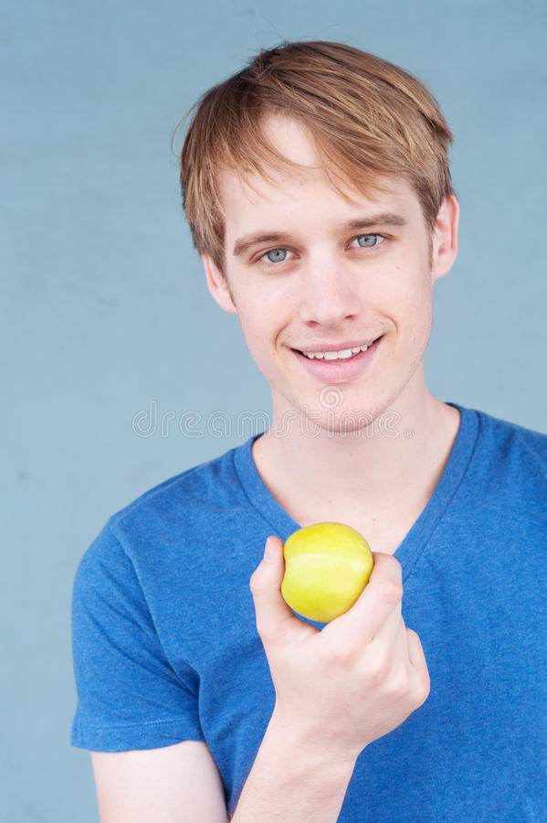 Portrait of a young man with an apple stock photo