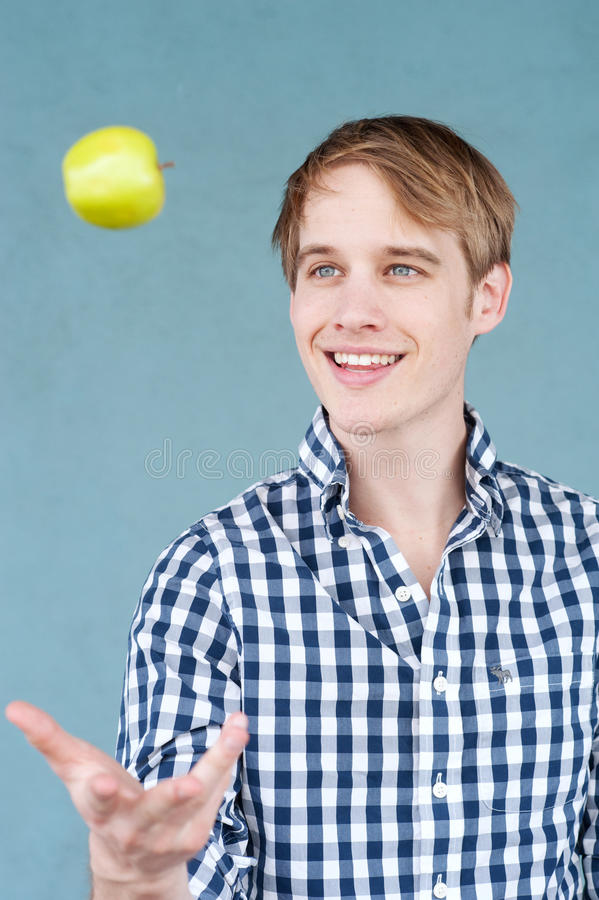 Portrait of a young man with an apple stock photography