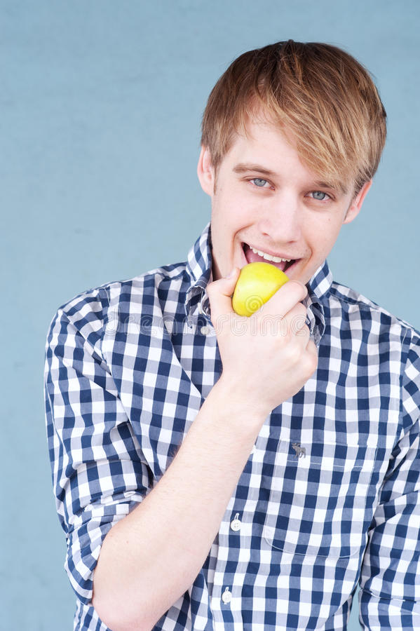 Portrait of a young man with an apple stock image