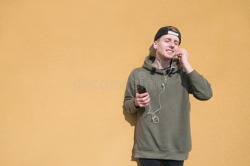 Portrait of a young man on the background of an orange wall while listening to music in headphones. A teenager in a cap stands on the background of a colored royalty free stock image