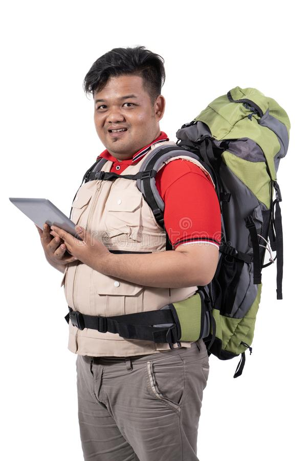 Portrait of young man backpacker standing holding digital tablet stock images