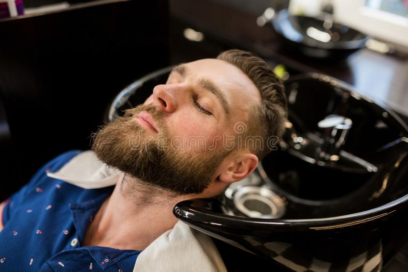 Young man in barber shop waiting for washing hair stock photos